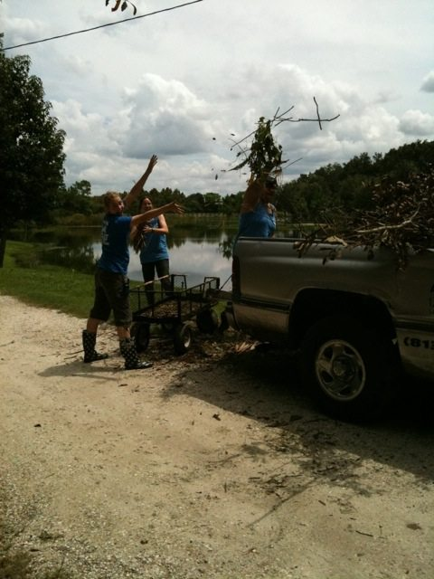 Interns Heave Tree Trimmings into Old Truck