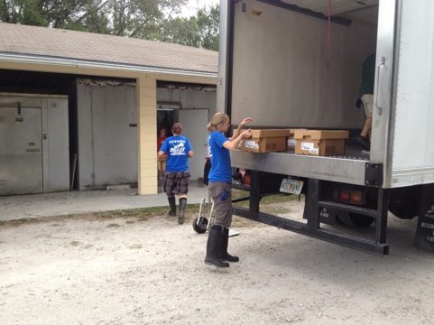 Meanwhile a truckload of meat arrives so volunteers and interns unload