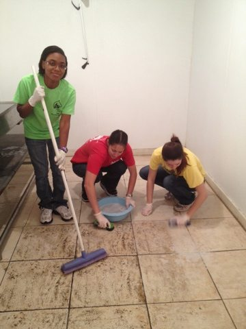 Volunteers and Advocats scrubbing the floor of the cooler