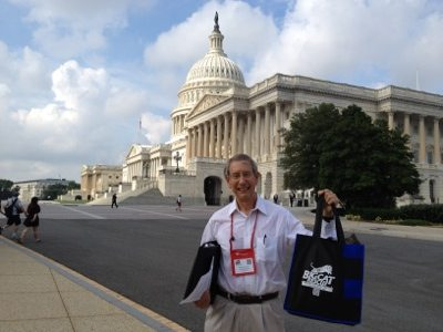 Howard Baskin holds up the conference bag w/ Big Cat Rescue's logo in front of the capitol