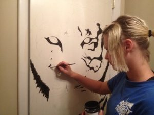 Intern Nicole paints on the back of the door in gift shop