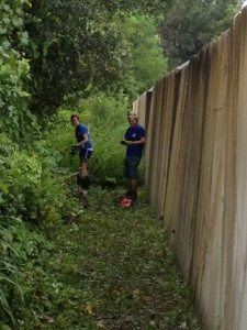 Interns clean brush away from outside perimeter wall